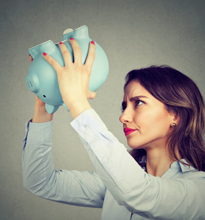 woman turning over a piggy bank