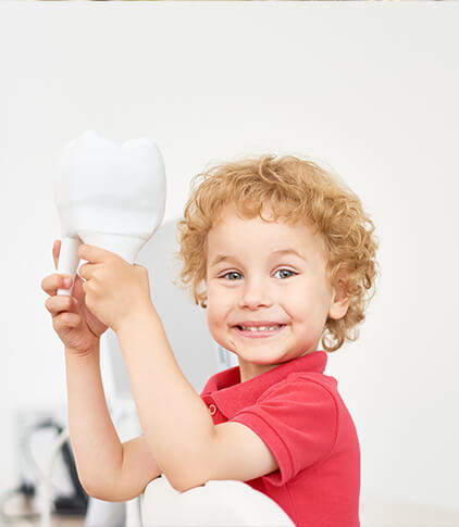 smiling little boy holding a large model tooth